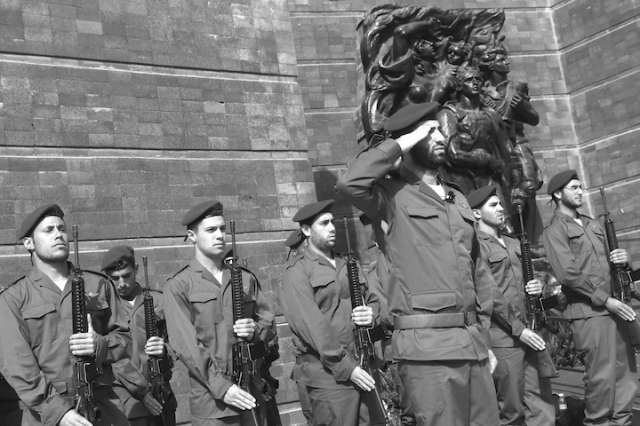 Israeli soldiers stand in a salute by a monument