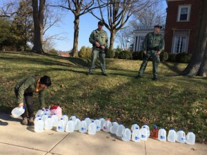 A woman distributes drinking water on the Governor's lawn for the residents of  impacted by the Freedom Industries chemical spill.