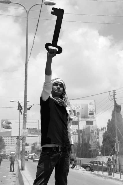 Palestinian Man Holds Up a Huge Key