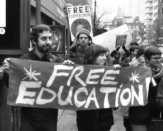 "Students Hold Up a Sign that Says ""Free Education."""