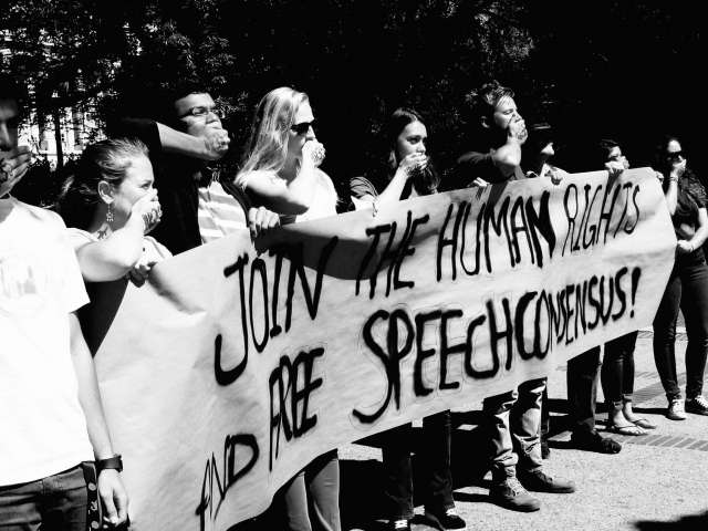 """Protestors hold a sign that says, """"Join the human rights and free speech consensus"""" and cover their mouths."""
