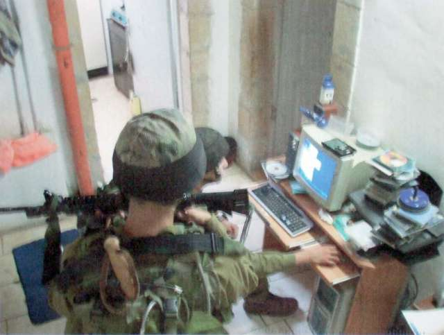 Soldiers inspect computer and its usage.
