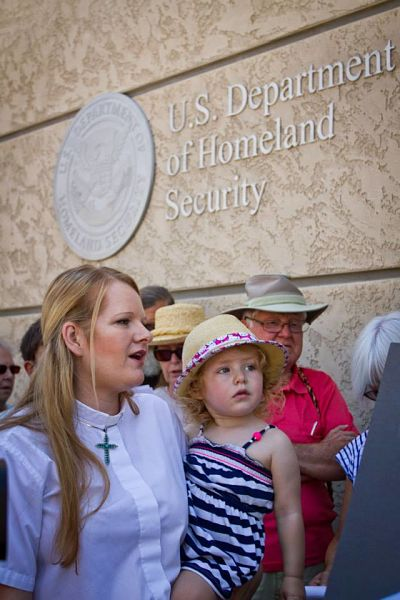 A reverend holding her daughter stands in front of the U.S. Department of Homeland Security.