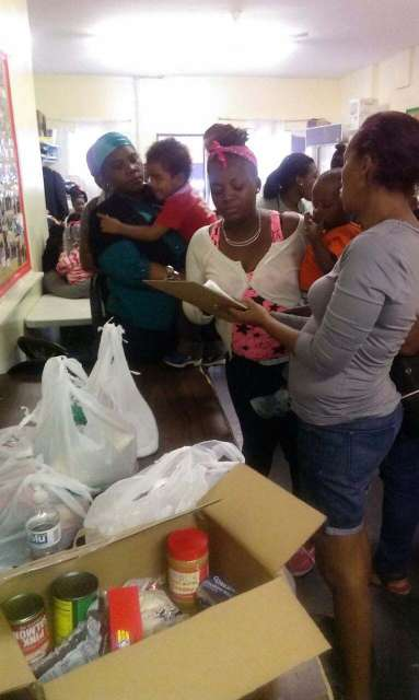 Several people stand, some waiting to pick up food donations on a table.
