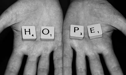 "Hands holding Scrabble tiles spelling out ""hope"""