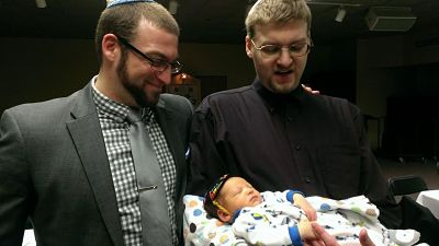 Two men look down on a baby.