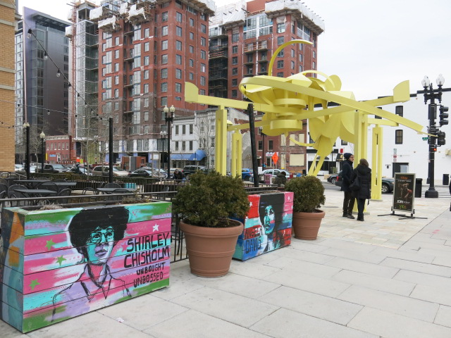 Flower-box murals of Shirley Chisholm and Angela Davis.