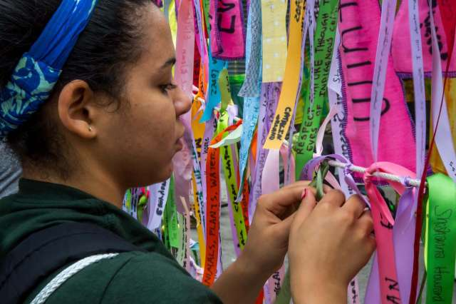 Women ties ribbons with words written on them together.