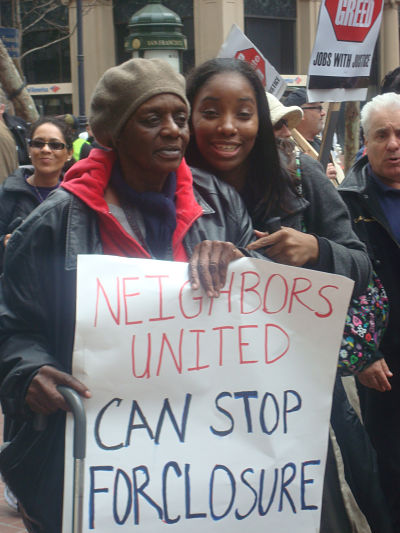 "Protesters hold up a sign saying, ""Neighbors United can stop foreclosure."""