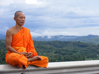 A monk sits in meditation by a view of the sky.