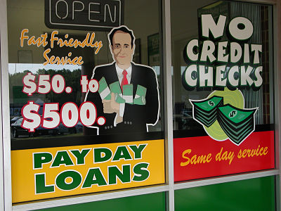 A look at the window advertisements of a payday loan office.