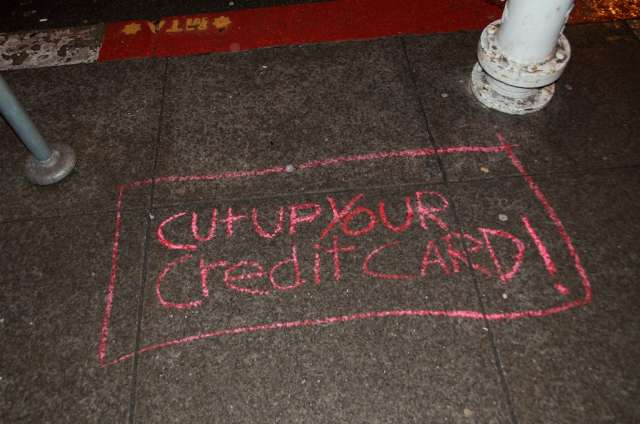 Chalk writing on the sidewalk, reading: Cut up your credit card!
