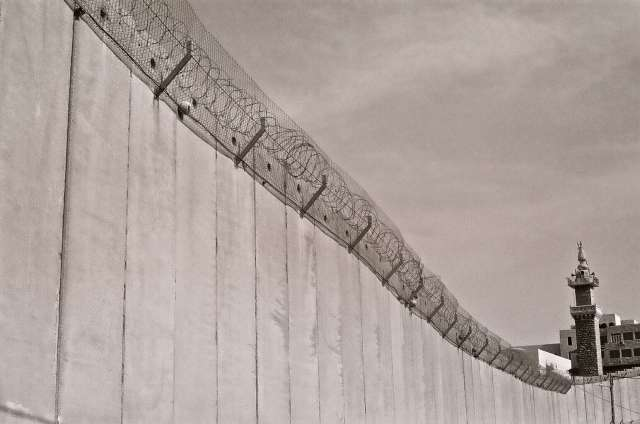 Wall with barbed wire separating two neighborhoods.