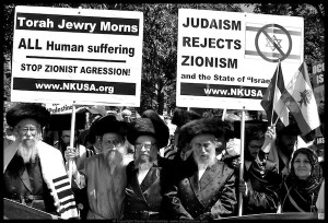 Jewish protestors holding up anti-Zionist signs.