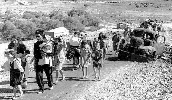 Palestinian refugees walking down a road.