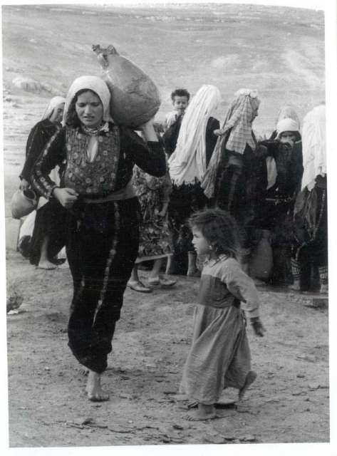 A Palestinian woman carries a jug with a child.