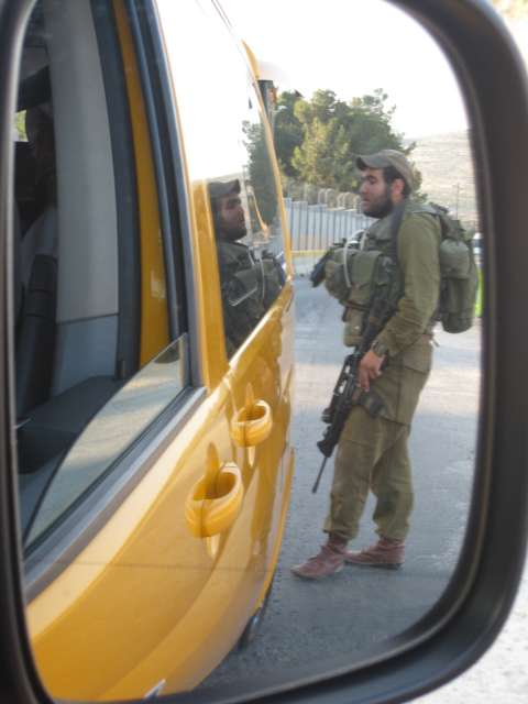 Soldier with gun at checkpoint on the way to Bil'in from Jenin.