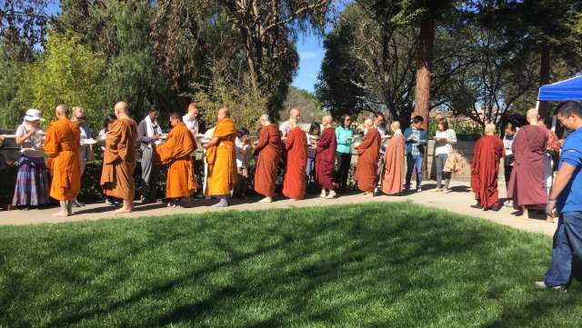 Buddhist monks wearing old robes walking in a park.