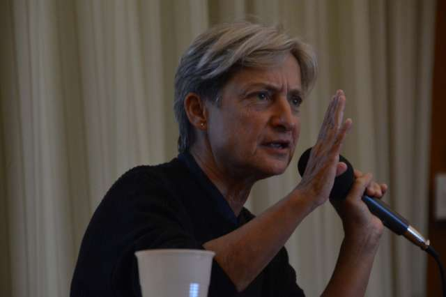 Judith Butler speaking on a microphone