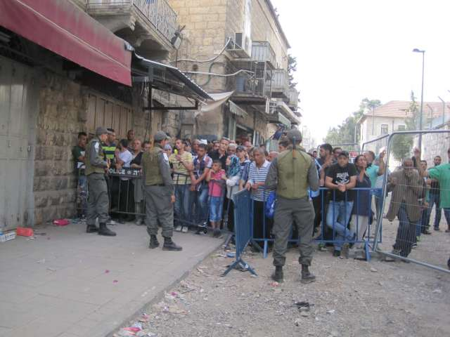 Israeli soldiers block Palestinians from entering the street.