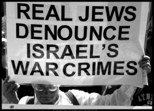 Man holding sign that says Real Jews denounce Israel's war crimes