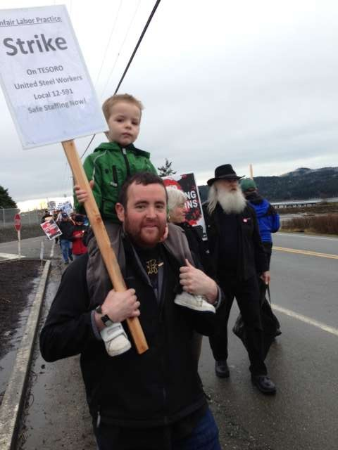 A man with a picket sign carrying his son on his shoulders.