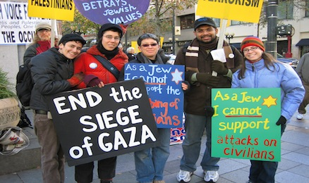 Jewish students holding signs protesting against Israeli occupation of Palestine.
