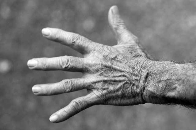 A black and white photograph of an old person's hand.