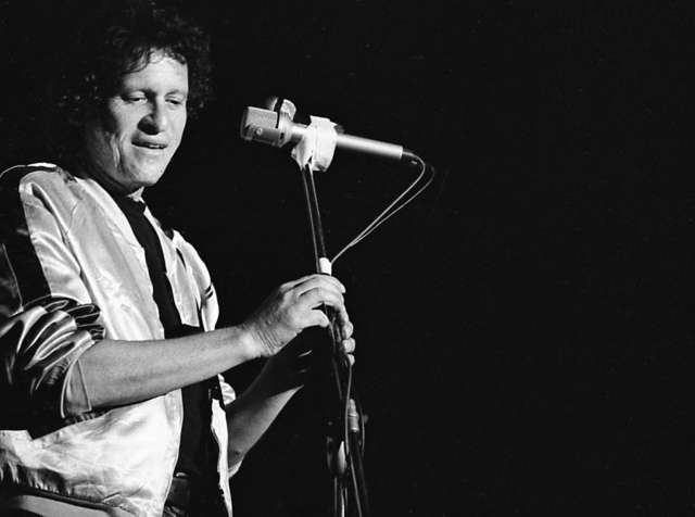 Paul Krassner at a microphone.