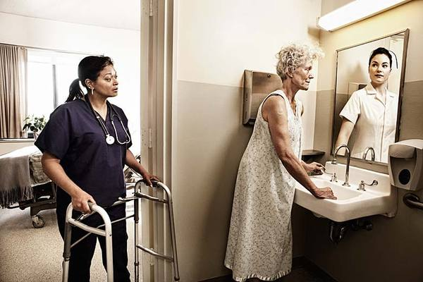 An elderly woman looking in the mirror at a reflection of her younger self whie her caretaker waits with a walker behind her.