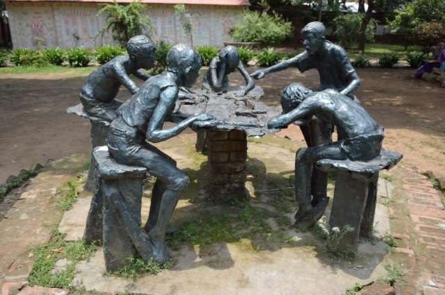 Statue of children having a discussion around a table.