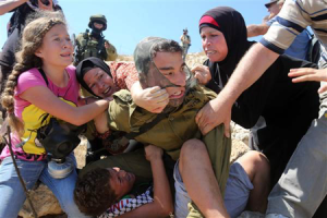 Image of people struggling, armed soldiers in the background.