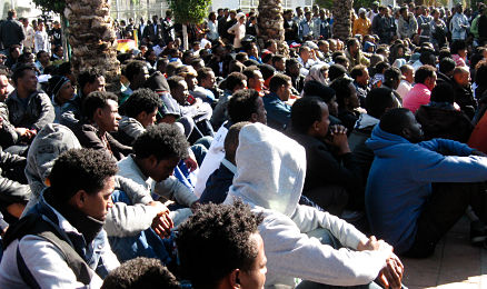 Group of African refugees in Israel gathered, some standing, some sitting, in a public space.