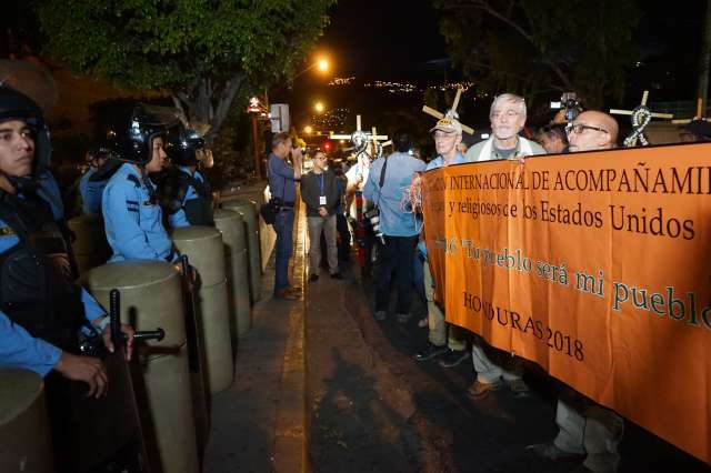 Emergency delegation to Honduras marching with banner