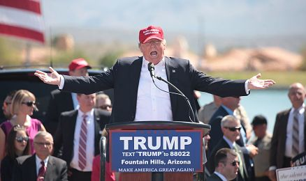 Image of President Trump speaking at a rally, wearing a red cap, with his arms spread wide