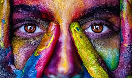 Image of a person with lots of color on their face, staring into camera
