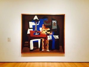 Picasso painting, distorted colorful figures, hanging on white wall