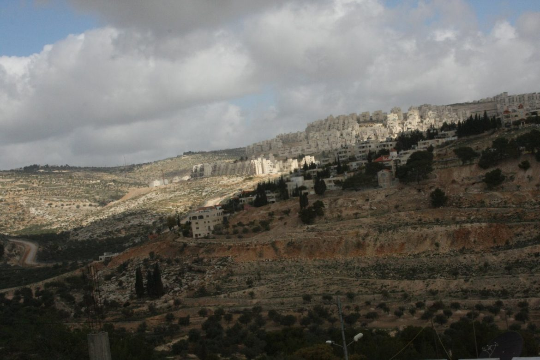 Image of buildings on hillside, half in shadow