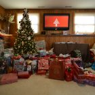 Image of large Christmas tree with a lot of presents underneath and around the tree