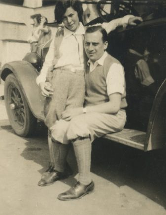 woman standing next to man sitting on footstep of car