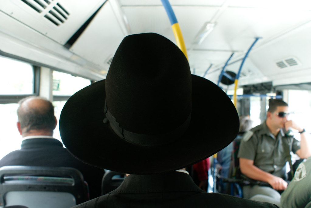 man standing on bus with large black hat