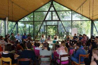 People sitting in concentric circles in a large tent with glass sides, sunlight coming in and trees out the window