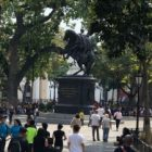 people standing in plaza staring at statue
