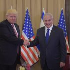 Trump and Netanyahu shaking hands in front of American and Israeli flags