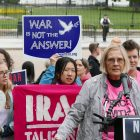 Image of a protest against war with Iran. Woman speaking at podium
