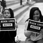 "Two black girls holding signs that say ""Black Lives Matter"""